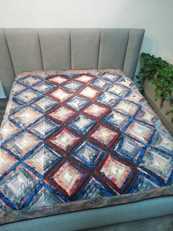 lovos užtiesalas su rombų ornamentais padėtas ant lovos