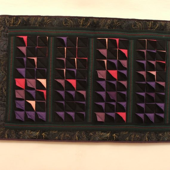 Tamsių spalvų sieninis skiautinis pakabintas ant sienos