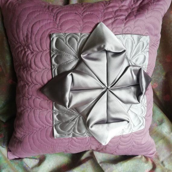 dekoratyvinė violetinė pagalvėlė žaliame fone