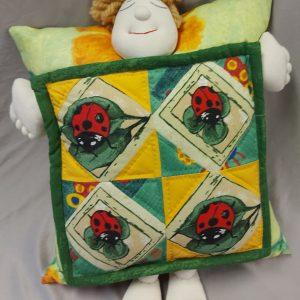 rankų darbo vaikiška pagalvė su boružėlėmis ir pagalvę apkabinusia lėle