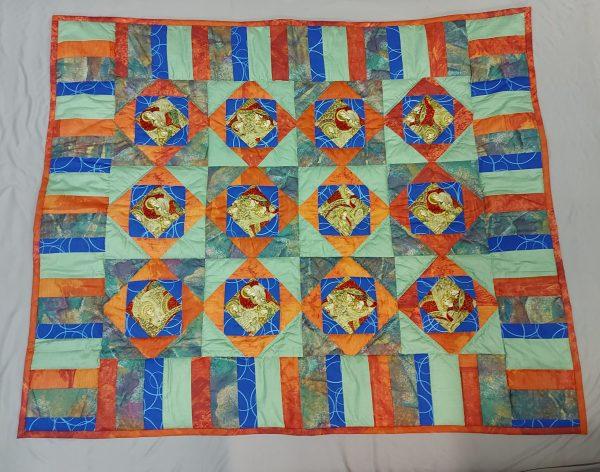 rankų darbo vaikiška antklodė pasiūta iš ryškių spalvų skiaučių baltame fone