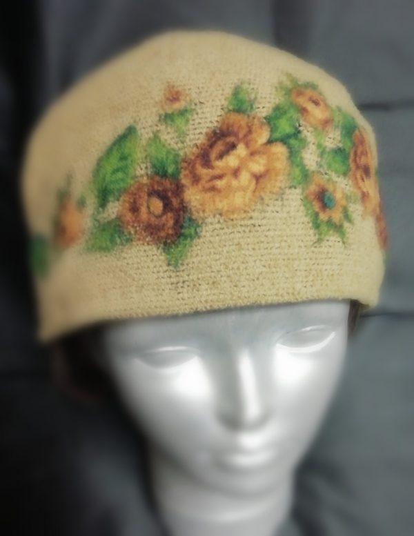 rankų darbo vilnonė kepurė su rožėmis uždėta ant manekeno galvos