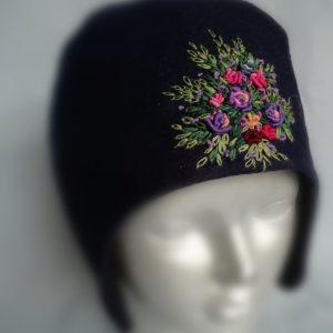 rankų darbo vilnonė kepurė su ausytėmis uždėta ant manekeno galvos
